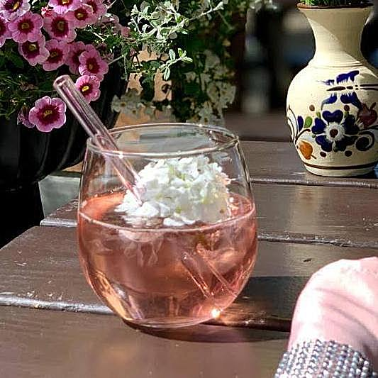 Photo of peach-colored drink with floating white flower and a 6-inch glass straw by ToMA Glass Straws.