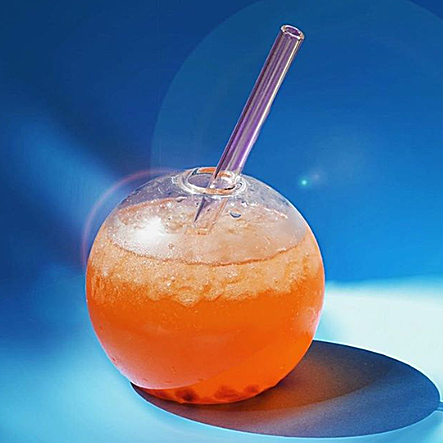 Photo of orange drink in round globe glass with 6-inch glass straw by ToMA Glass Straws. Photo by Kimberly @chix.ology on Instagram