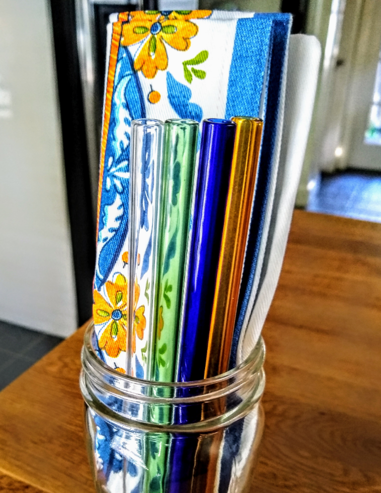 glass jar with cloth napkin and glass straws on wood kitchen counter