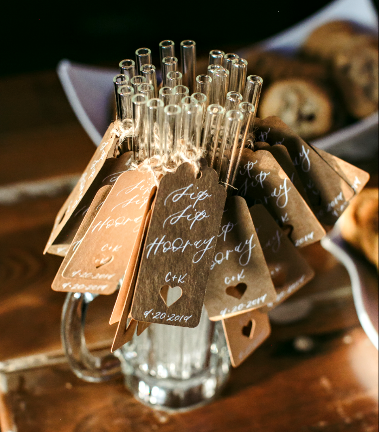 Clear glass mug filled with clear ToMA glass straws with handprinted tags for wedding favors for guests.