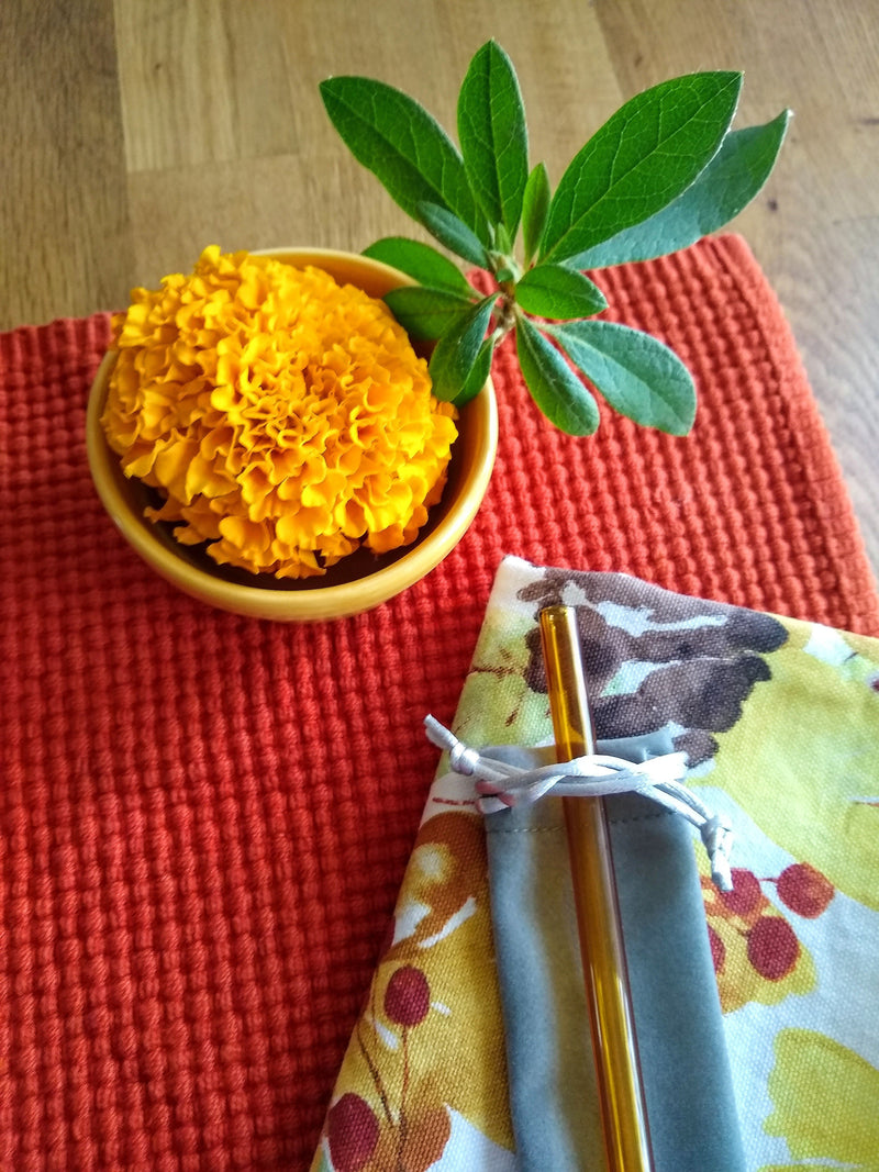 Photo of ToMA glass straw in artisanal amber on sage velveteen drawstring bag on autumn print napkin. Orange placemat, marigold in yellow vase, wood tabletop.