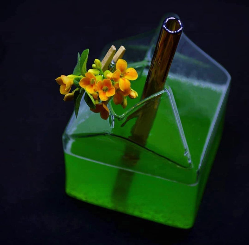 Photo by Melisa Lapido of ToMA glass straw in artisanal amber in clear milk carton glass with green cocktail and yellow flower garnish.