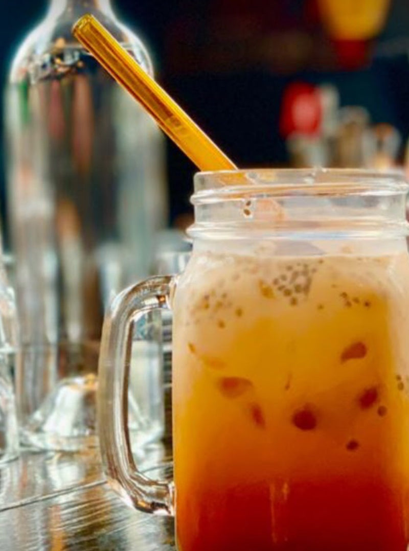Photo of a ToMA glass straw in artisanal amber in a jar glass of Vietnamese iced tea or Thai iced coffee. Wholesale glass straws for businesses and events.