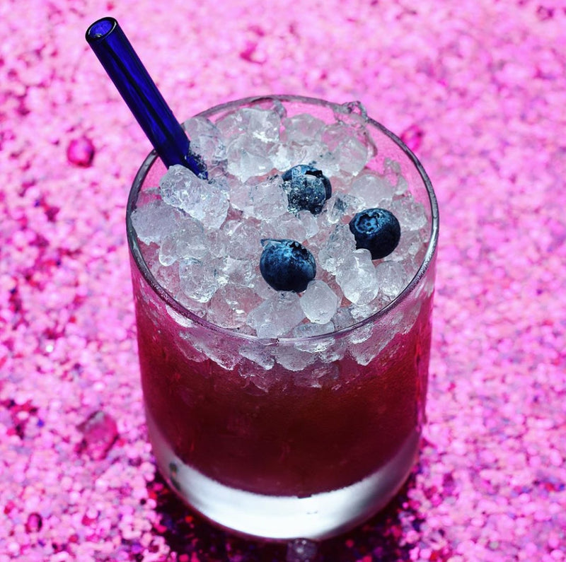 Photo by Kimberly Lashbrook of 6-inch ToMA glass straw in pacific blue in clear glass filled with crushed ice and pink cocktail with blueberry garnish on pink background.