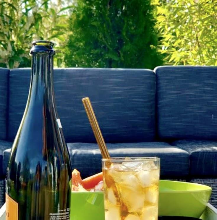 Photo of ToMA glass straw in artisanal amber in iced-filled glass on outdoor table with snacks. Gray outdoor sofa, treen, and bamboo in background.