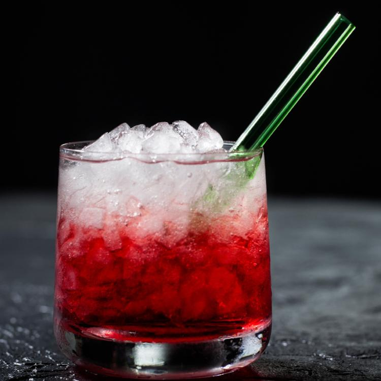 Photo of red drink with white crushed ice featuring a ToMA glass straw in forest park green. Beautiful, durable, affordable, reusable glass straws for bars, restaurants, cafes, events, weddings, and home use.