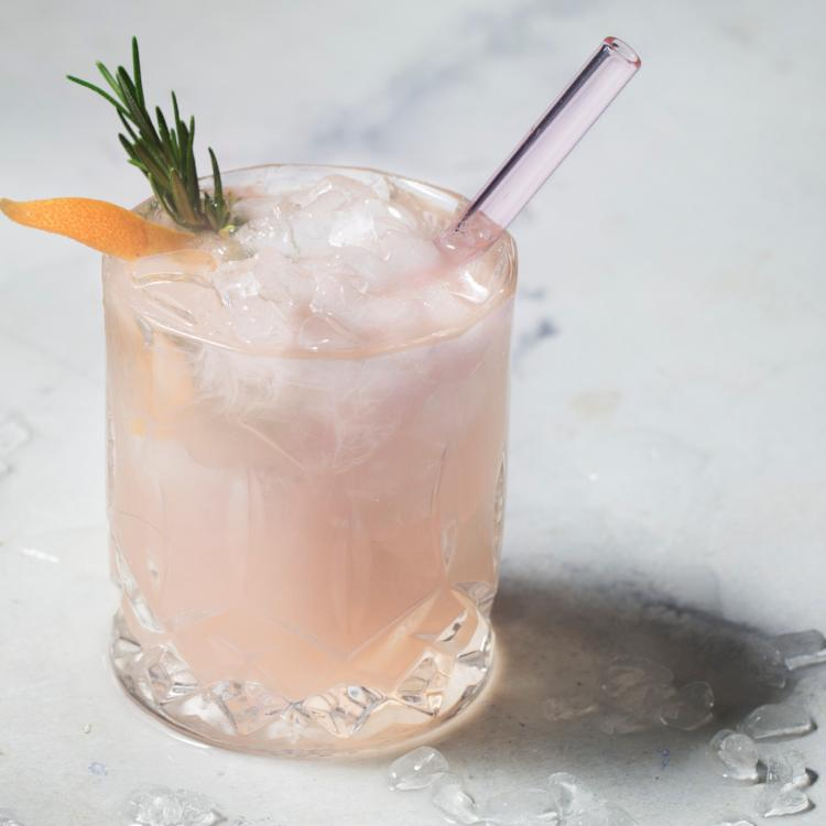 Photo of pale pink drink garnished with rosemary and orange peel with ToMA glass straw in rose garden pink. Beautiful, durable, affordable, reusable glass straws for bars, restaurants, cafes, weddings, home bar use.