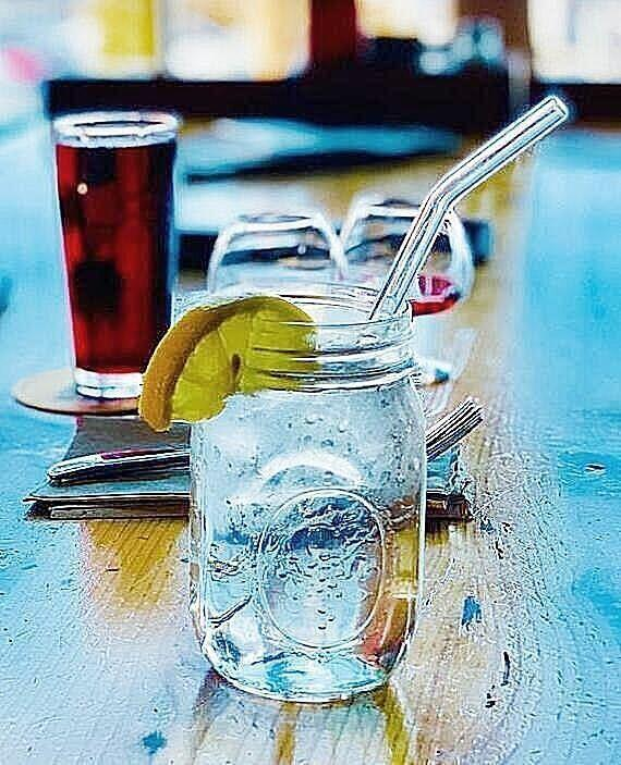 ToMA glass straw in bent glacier clear in mason jar of water with citrus slice on wood table in restaurant setting.