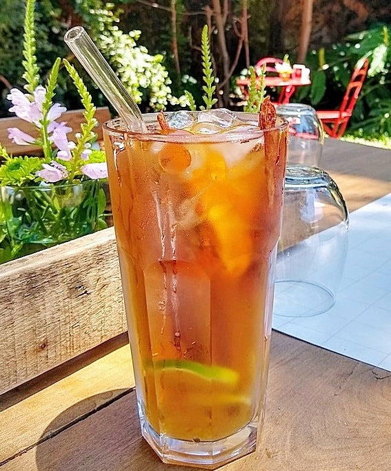 Best 9-inch bent ToMA glass straw in glacier clear in tall glass of iced tea on outdoor picnic table in restaurant garden area.