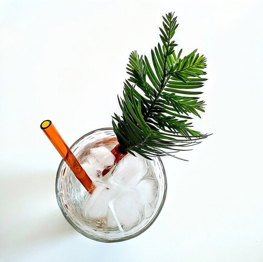 ToMA glass straw in artisanal amber in clear glass with ice and clear beverage. Greenery garnish, white background, #getclearin2020