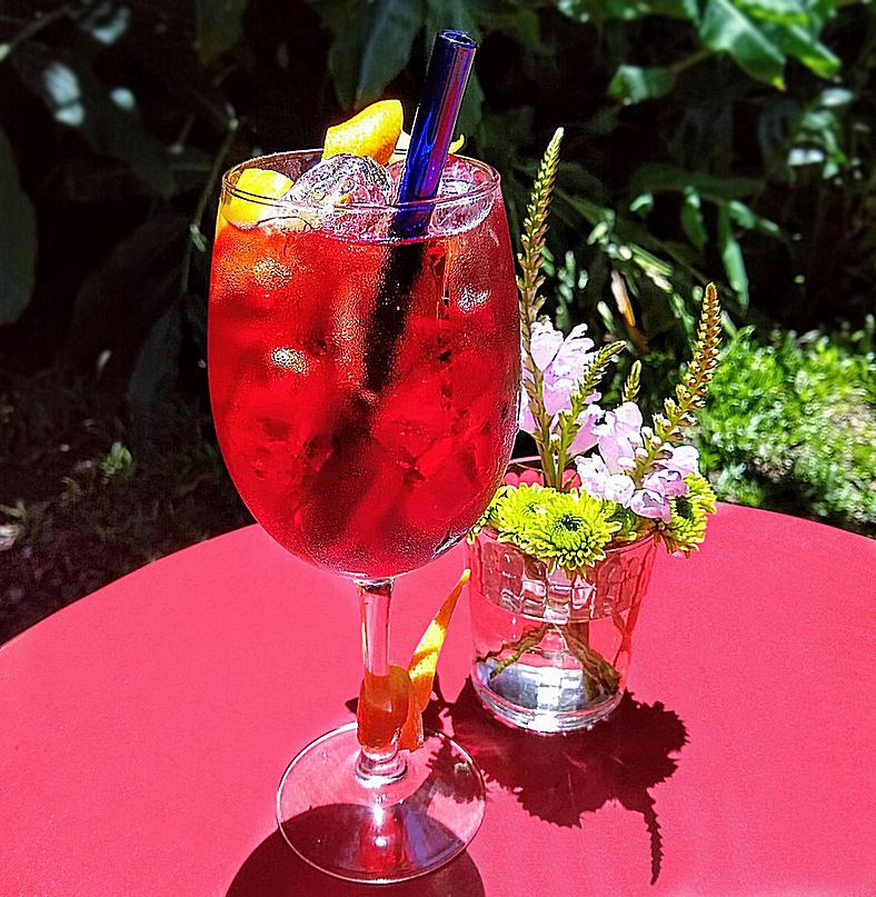 ToMA glass straw in pacific blue in aperol spritz cocktail on red outdoor table with small vase of fresh flowers. Green foliage background.