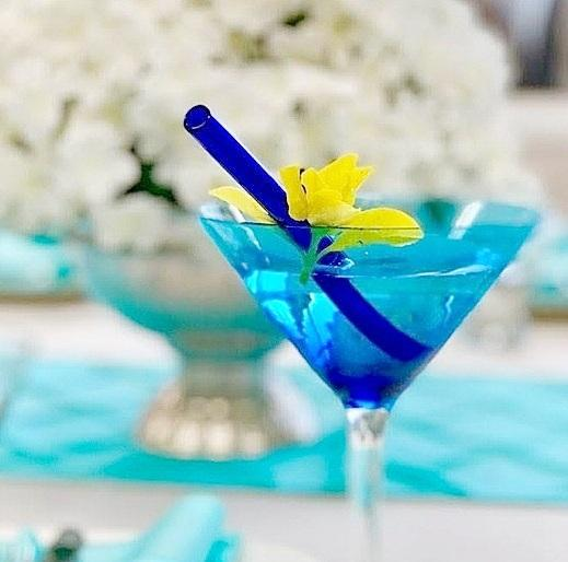 Photo of 6-inch ToMA glass straw in pacific blue in blue martini glass as signature drink at wedding with yellow flower garnish on bridal table.