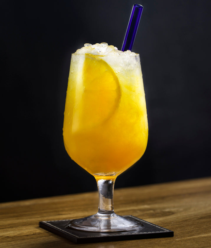 Photo of an orange juice cocktail featuring a reusable 6-inch ToMA glass straw in pacific blue. Part of the Seascape Package, a special summer deal for bars, restaurants, events, weddings. Photo: Magela Crosignani