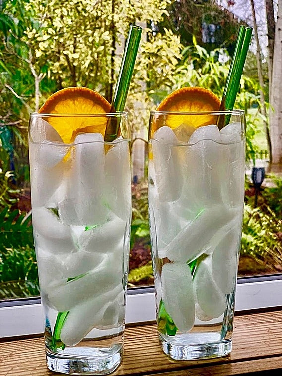 Photo of two tall glasses of clear liquid with 9-inch glass straws in forest park green by ToMA Glass Straws. Part of the Party Pack for home bars, home bartending.