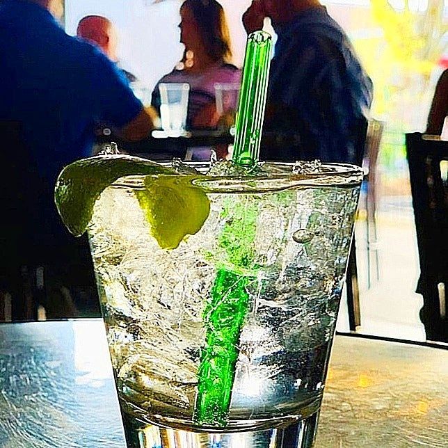 ToMA glass straw in forest green in clear cocktail with lime garnish on table in outdoor patio with fall leaves.
