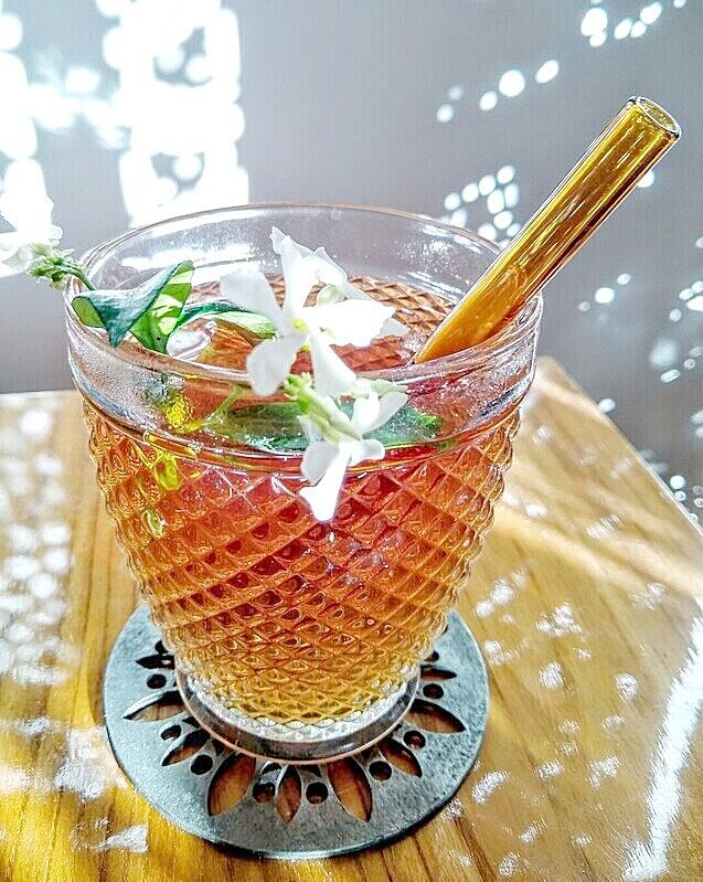 Clear glass with hot jasmine tea and jasmine blossom garnish with ToMA glass straw in artisanal amber. Shadows from carved screen, cut silver coaster on wood table.