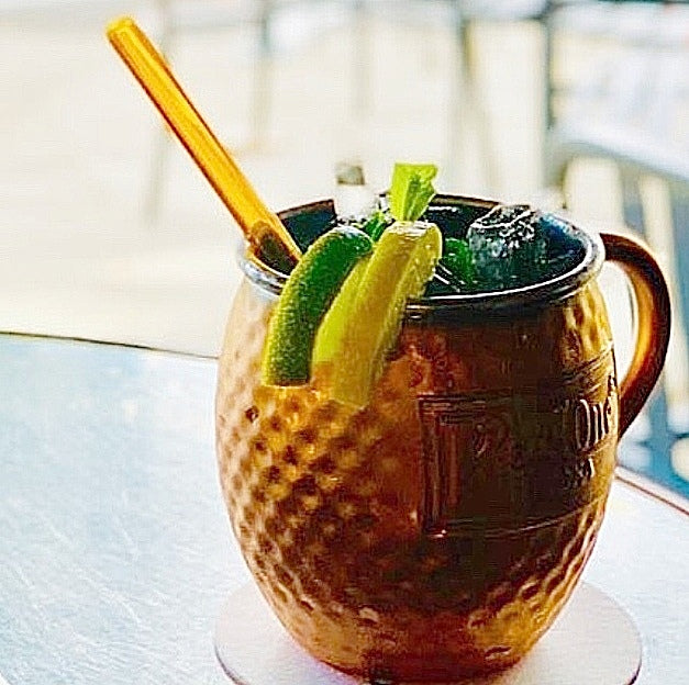ToMA glass straw in artisanal amber in copper mug Moscow Mule with ice, lime lemon slices.
