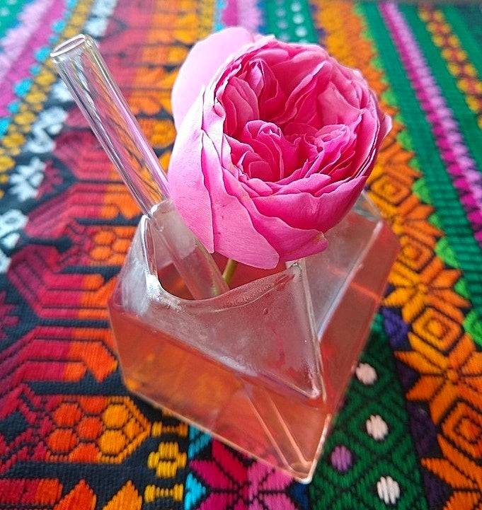 ToMA glass straw in glacier clear in clear milk carton glass with herbal tea and rose garnish on Mexican cloth.
