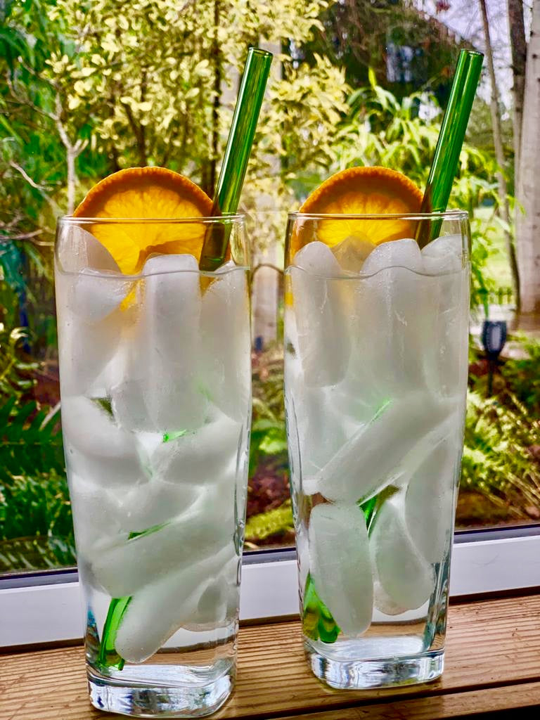 Two ToMA glass straws in forest green in two ice-filled glasses with orange garnish on window sill with fall background.
