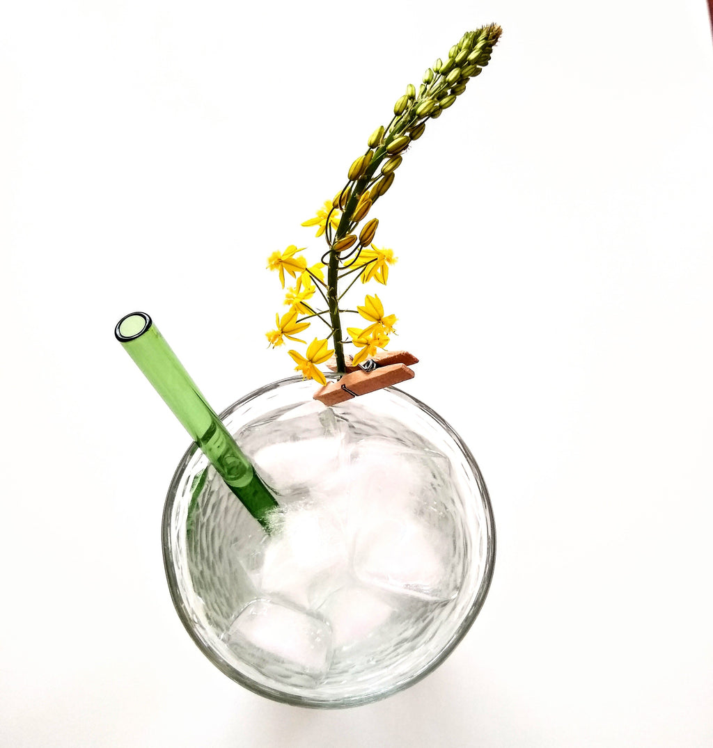 ToMA glass straw in forest green in clear glass with yellow flower garnish.