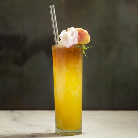 Photo of tall orange cocktail garnished with two roses featuring a 9-inch glass straw in glacier clear by ToMA Glass Straws. Photo: Magela Crosignani