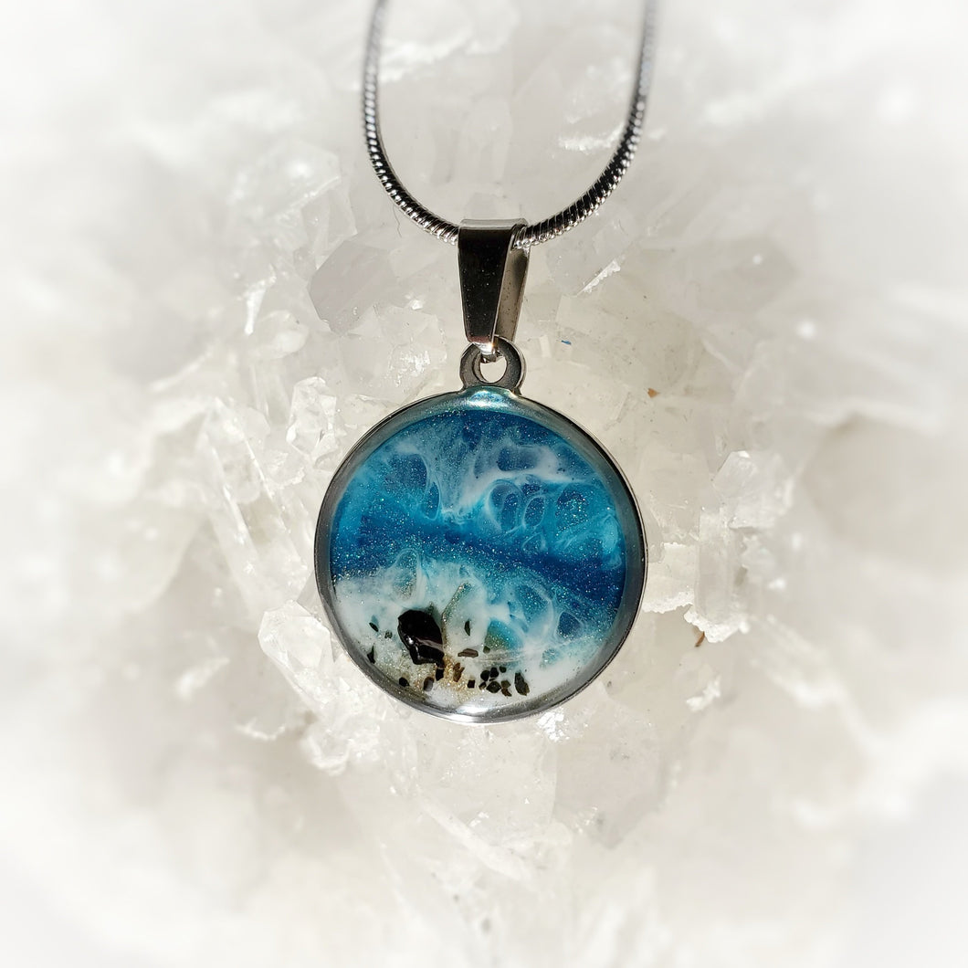 This round 18mm pendant in a stainless steel base contains the most intricate beach inspired resin art created with shimmery turquoise and deep blue, and accented with metallic gold tones and black tourmaline pieces. Finished with a shiny, reflective clear coat of resin for long lasting beauty.  This item is hand painted resin art, so absolutely unique!