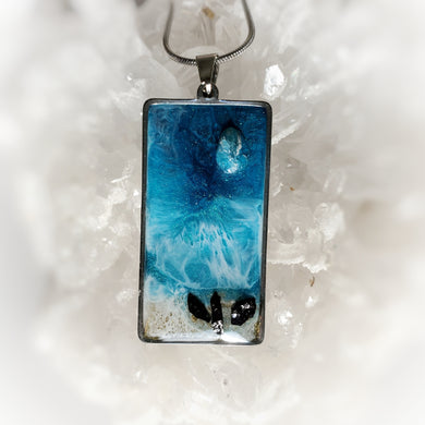 This 20x40mm pendant in a stainless steel base contains the most intricate beach inspired resin art created with shimmery turquoise and deep blue, and accented with metallic gold, a genuine Apatire stone and three black tourmaline pieces. Finished with a shiny, reflective clear coat of resin for long lasting beauty.  This item is hand painted resin art, so absolutely unique!