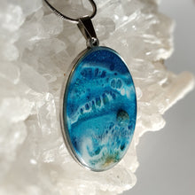 Load image into Gallery viewer, This oval 30x40mm pendant in a stainless steel base contains the most intricate resin beach inspired art created with shimmery turquoise and deep blue, and accented with metallic gold and an Apatite stone. Finished with a shiny, reflective clear coat of resin for long lasting beauty.  This item is hand painted resin art, so absolutely unique!