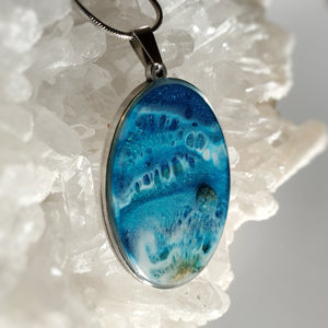 This oval 30x40mm pendant in a stainless steel base contains the most intricate resin beach inspired art created with shimmery turquoise and deep blue, and accented with metallic gold and an Apatite stone. Finished with a shiny, reflective clear coat of resin for long lasting beauty.  This item is hand painted resin art, so absolutely unique!