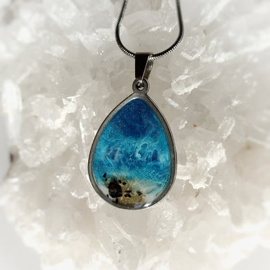 This teardrop 18x25mm pendant in a stainless steel base contains the most intricate resin beach inspired art created with shimmery turquoise and deep blue, and accented with metallic gold and Black Tourmaline pieces. Finished with a shiny, reflective clear coat of resin for long lasting beauty.  This item is hand painted resin art, so absolutely unique!