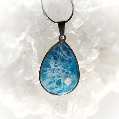 This teardrop 18x25mm pendant in a stainless steel base contains the most intricate resin beach inspired art created with shimmery turquoise and deep blue, and accented with Rhodizite crystal. Finished with a shiny, reflective clear coat of resin for long lasting beauty.  This item is hand painted resin art, so absolutely unique!