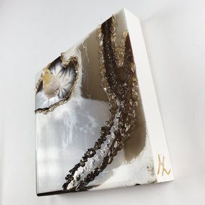 This geode inspired resin art piece was created white and brown with subtle touches of metallic gold, embellished with real Quartz cluster and Citrine chips, as well as metal flakes adding depth and interest. The translucent brown gives the illusion of floating white lacing details, and the cluster corner is made to emanate growth from within. Guaranteed to be unique, and it's hand made with lots of attention and positive intention.
