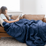 queen size weighted blanket being used by female on couch