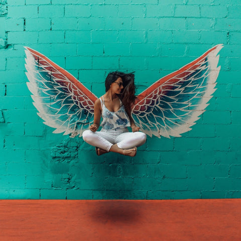 Girl in Easy Pose, floating in front of Angel Wings.