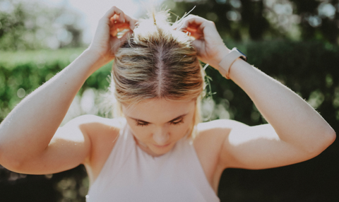 blonde girl fixing her hair
