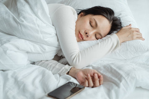 Women sleeps with her head on a pillow and a phone laying next to her.