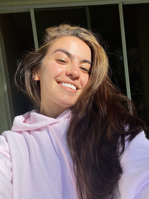 girl with brown hair and pink hoodie smiling with sun on face