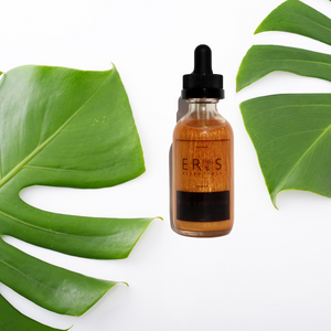 gold body oil with green leaves