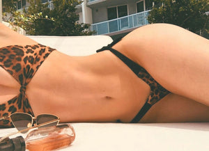 Girl with leopard bikini laying on beach chair