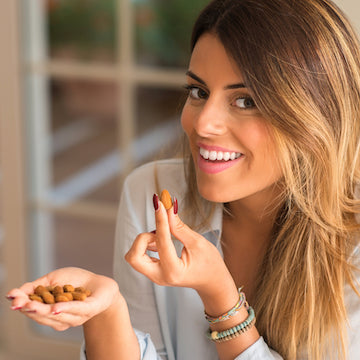 Attractive Woman Eating Organic Activated Almonds