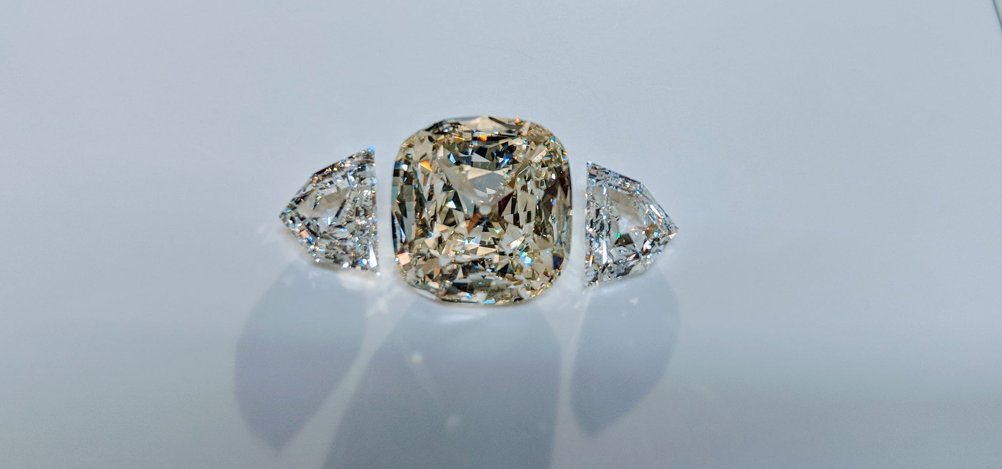 64Facets Diamond Setting with Two Half Shield Step-Cut Diamonds as Side Stones