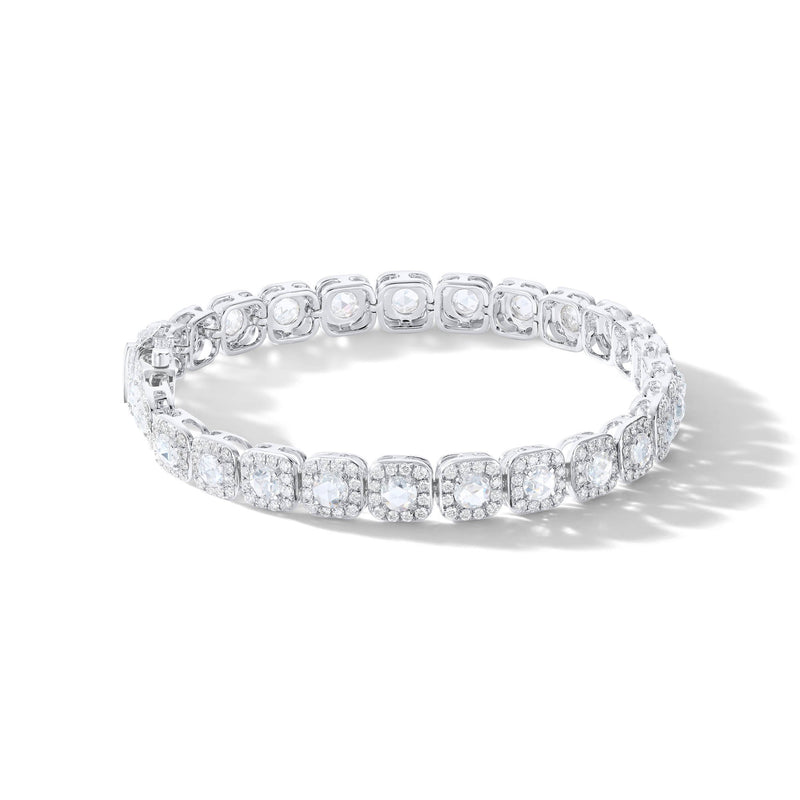 Diamond Tennis Bracelet On a hand. Rose cut diamonds accented by micro pave accents in a cushion shape.
