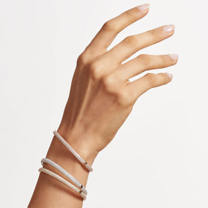 Model wearing Brilliant Cut Micro Pave Diamond Bangle Bracelets in 18k Rose, White and Yellow Gold.