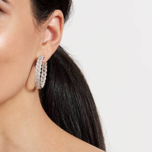 Model wearing 64Facets 18k rose gold and diamond hoop earrings. Rose cut diamonds accented by smaller brilliant cut diamonds.