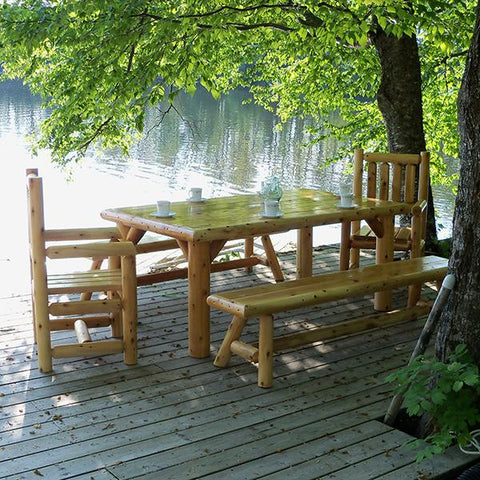 Outdoor dining table and seating close to a lake under a tree