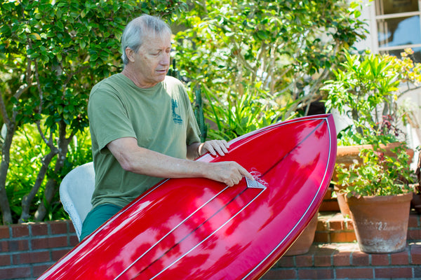 Rich Pavel pointing out his Choice label logo on a red surfboard