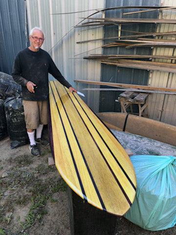 Jim Phillips standing next to a shaped surfboard