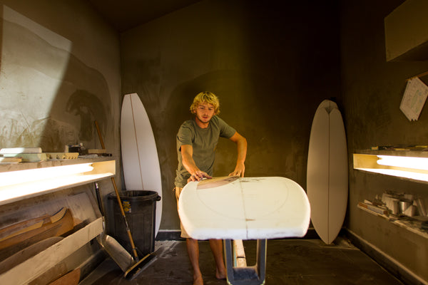 Tyler Warren shaping a surfboard