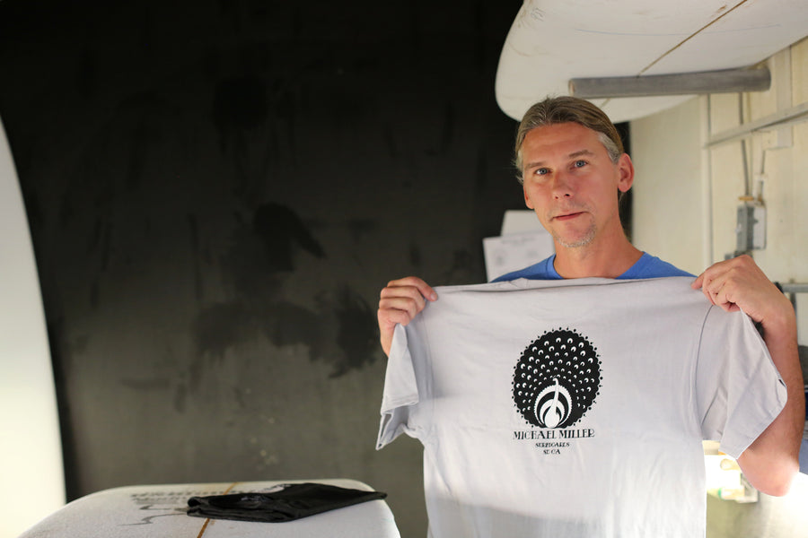 Michael Miller surfboard shaper standing in his shaping room holding his Peacock surf t-shirt