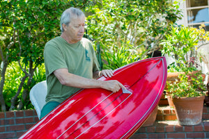 Rich Pavel pointing out his choice logo on a red surfboard